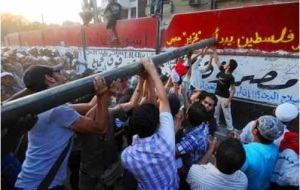 Egyptian protesters destroying a wall surrounding the Israeli Embassy in Cairo